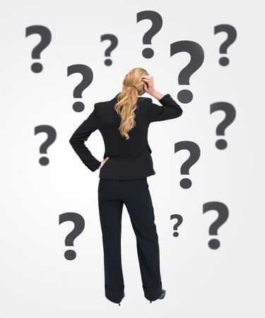 quizzical: Empresaria Quizzical con la espalda a la c�mara sobre fondo blanco con signos de interrogaci�n balck Foto de archivo