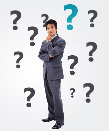 quizzical: Questioning businessman on white background with question marks