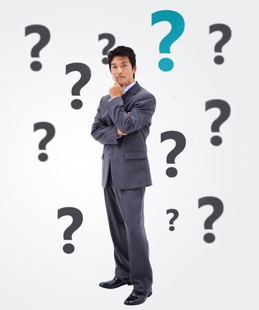 questionnement: Questionner homme d'affaires sur fond blanc avec des points d'interrogation