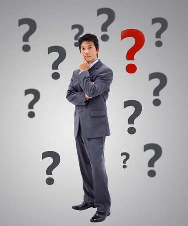 Businessman thinking surrounded by question marks on grey background photo