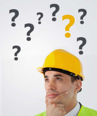 quizzical: Man in hard hat thinking on white background with question marks