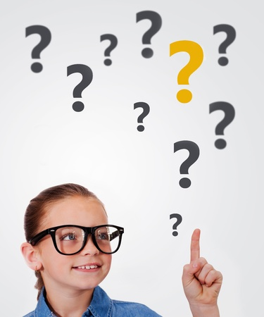 Curious child in glasses pointing up on white background with question marks photo