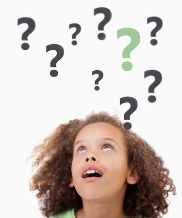 quizzical: Pensando ni�o con signos de interrogaci�n sobre su fondo blanco mirando hacia arriba Foto de archivo