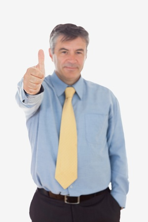 Portrait of businessman gesturing thumbs up against white background photo