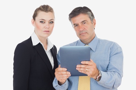 Serious business people with digital table against white background photo