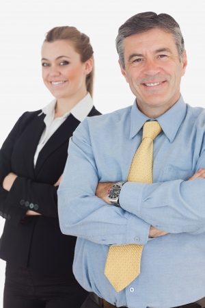 Portrait of happy business people with arms crossed standing against white background photo
