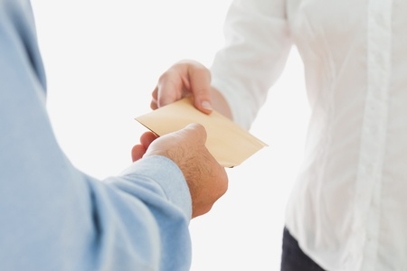 Close-up of businessman handing over envelop to businesswoman over white background Stock Photo - 18123294