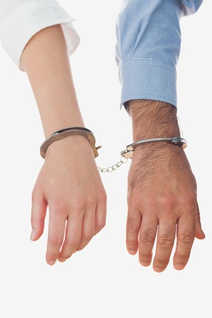Hands of business people in handcuffs over white background Stock Photo - 18123397