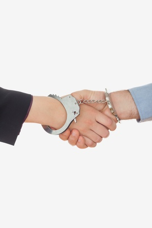 Handcuffed business partners shaking hands over white background Stock Photo - 18122953