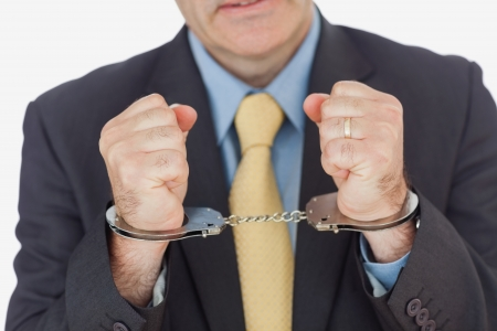 restraining device: Close-up of businessman with handcuffed hands over white background