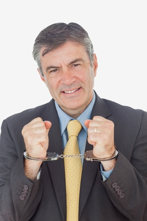 handcuffed hands: Portrait of businessman with handcuffed hands against white background