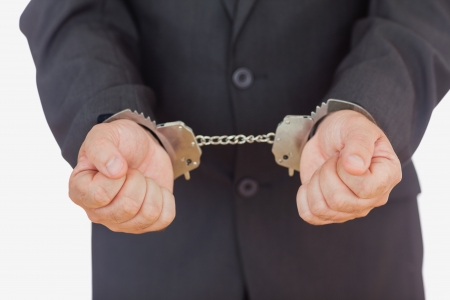 restraining device: Handcuffed businessman against white background