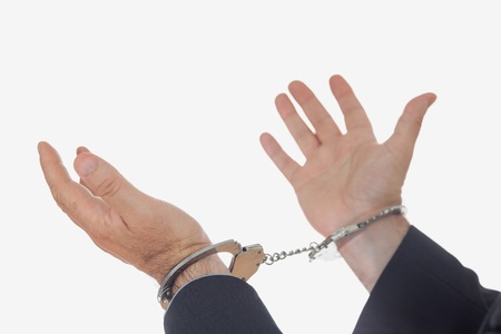 restraining device: Close-up of hands with handcuffs praying over white background
