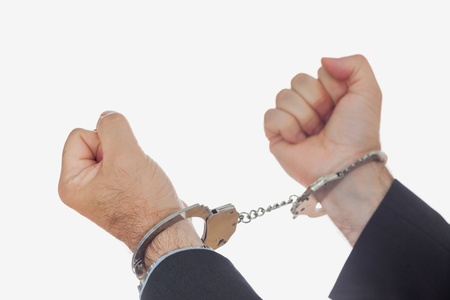 restraining device: Man in handcuffs clenching fists over white background Stock Photo