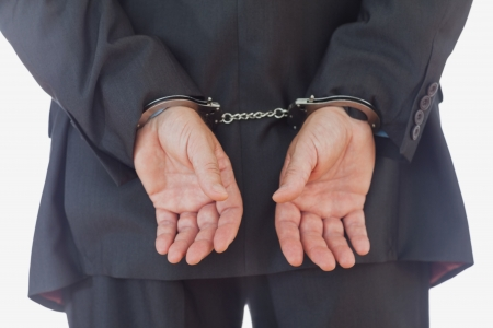 Rear view of businessman with handcuffs over white background photo