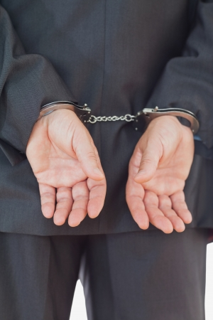 Rear view of businessman in suit with handcuffs photo