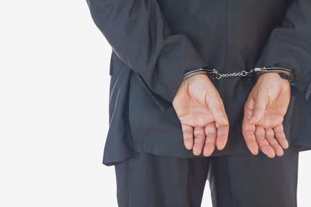 Businessman in handcuffs standing against white background photo
