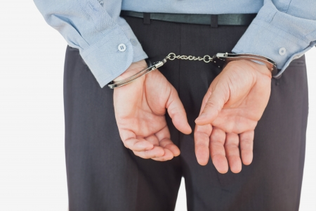restraining device: Rear view of businessman in formals with handcuffs standing against white background