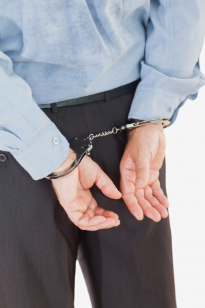 restraining device: Rear view of businessman in handcuffs standing isolated over white background Stock Photo