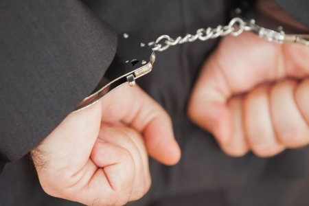 clenching fists: Close-up of hands in handcuffs clenching fists