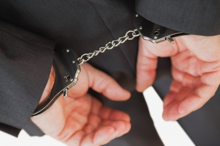 restraining device: Businessman with handcuffs over white background