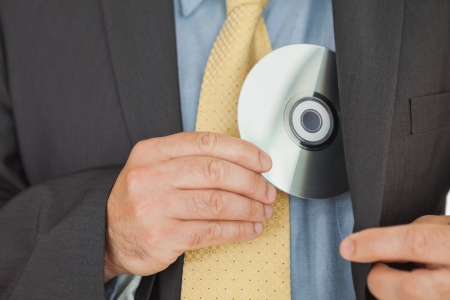 office politics: Close-up of businessman putting Compact disk in pocket Stock Photo