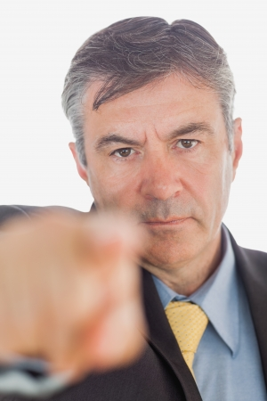 Portrait of angry businessman pointing over white background photo