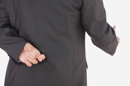 crossed fingers: Close-up of businessman with crossed fingers offering handshake over white background