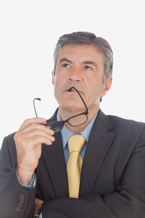 hair tie: Thoughtful mature businessman holding glasses as he looks up over white background Stock Photo