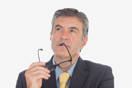 Thoughtful mature businessman with glasses looking up over white background photo