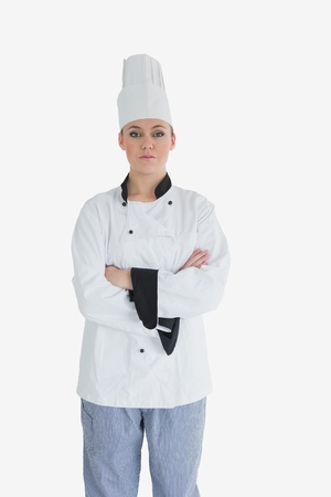 Portrait of female chef with arms crossed standing against white background photo