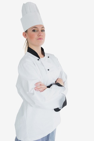 Portrait of confident female chef in uniform standing with arms crossed over white background photo