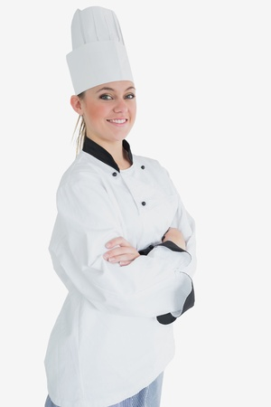 Portrait of happy female chef with arms crossed standing against white background photo