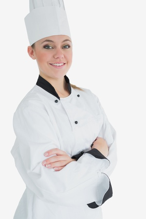 Portrait of confident female chef standing over white background photo