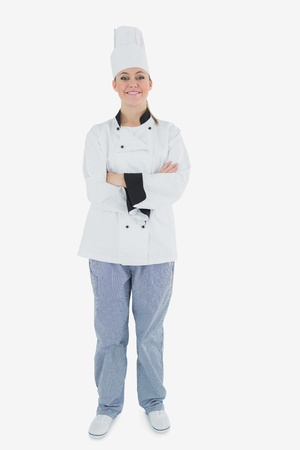 Full length portrait of happy chef standing with arms crossed over white background photo