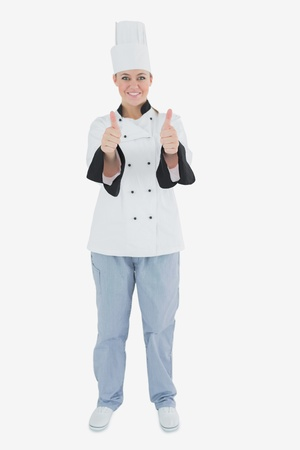 Full length portrait of female chef gesturing thumbs up sign over white background photo