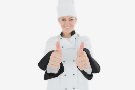 Portrait of happy female chef gesturing thumbs up over white baclground photo