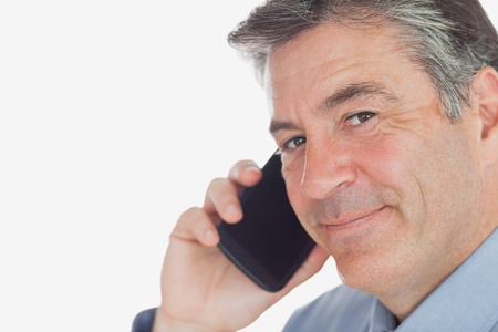 Portrait of mature businessman on call against white background photo