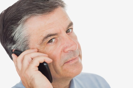 Close-up portrait of mature businessman using mobile phone against white background photo