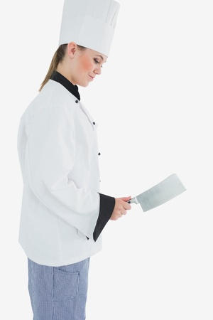 Side view of female chef holding meat cleaver as she smiles against white board photo