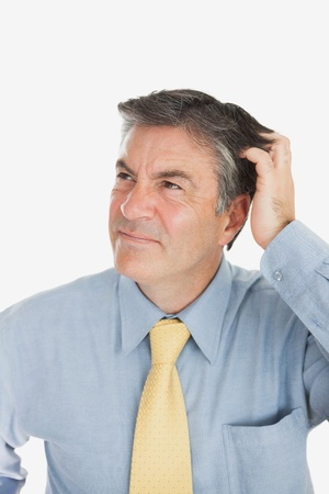 scratching head: Confused mature businessman scratching head against white background Stock Photo