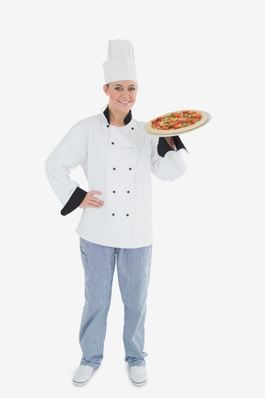 Full length of confident female chef holding pizza over white background photo