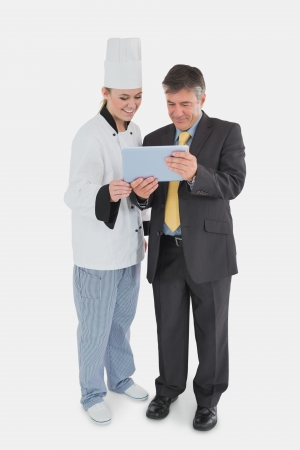 Full length of businessman and chef using digital tablet over white background photo