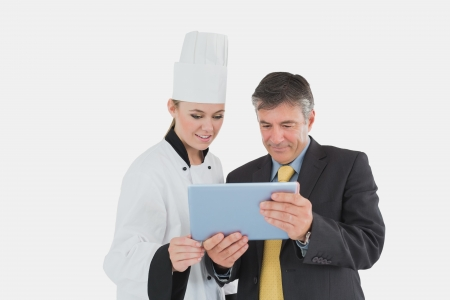 Mature businessman and female chef using digital tablet over white background photo