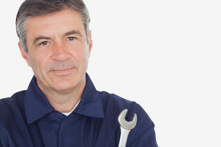 Close-up portrait of mature machanic with wrench against white background photo