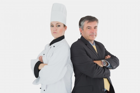 Portrait of businessman and chef standing back to back over white background photo