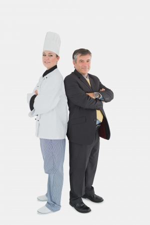 Full length portrait of businessman and female chef standing back to back against white background photo