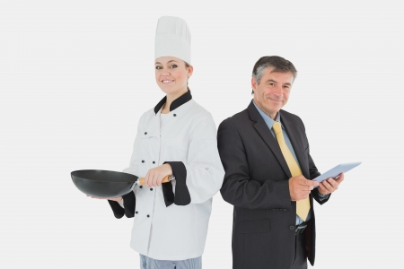 Portrait of businessman holding digital tablet and female chef with frying pan over white background photo