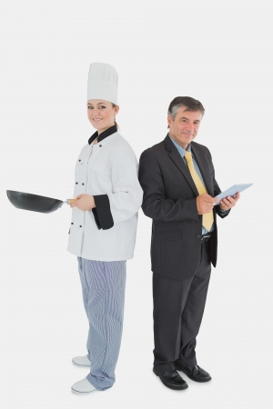Full length portrait of happy businessman holding digital tablet and female chef with frying pan over white background photo