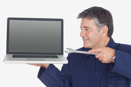 Mature male mechanic holding wrench and laptop over white background photo